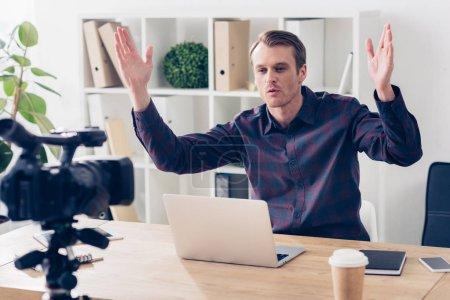 Foto de Blogger video hombre guapo en camiseta violeta grabando vlog y gesticular en oficina - Imagen libre de derechos