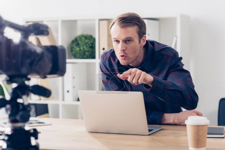 aggressive male video blogger recording vlog and pointing on camera in office