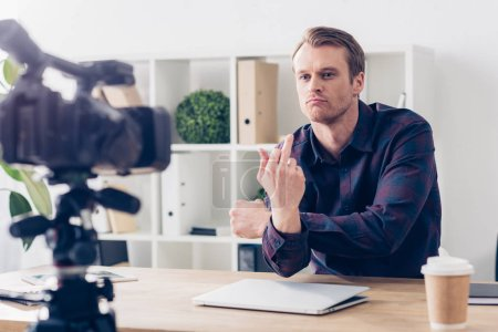 male video blogger recording vlog and showing middle finger in office