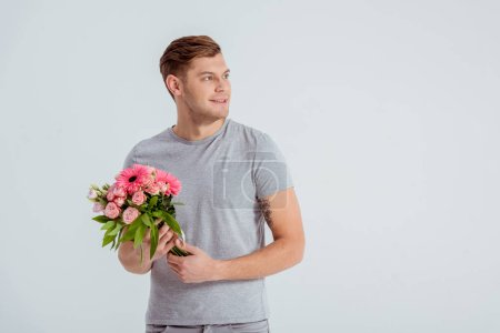 handsome man holding pink flower bouquet and looking away isolated on grey