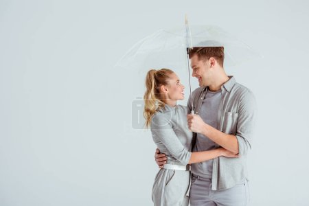 beautiful couple looking at each other and posing under transparent umbrella isolated on grey