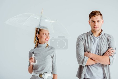 smiling woman holding transparent umbrella and standing near dissatisfied man with crossed arms isolated on grey