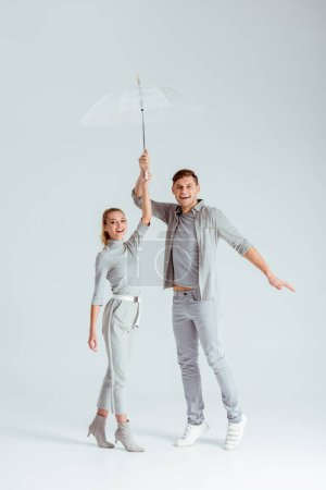 excited couple standing on tiptoe and posing with transparent umbrella on grey background