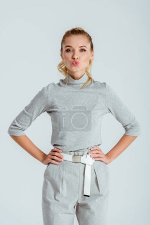 beautiful woman with duck face and hands on hips looking at camera isolated on grey