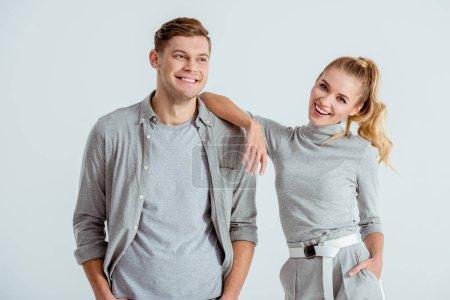 Photo pour Beau couple souriant, regardant la caméra et posant isolés sur gris - image libre de droit