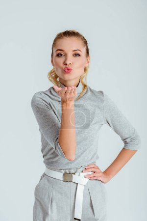 Beautiful woman giving air kiss and looking at camera isolated on grey