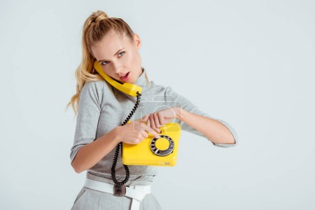 Photo for Beautiful woman dialing phone number on vintage yellow telephone isolated on grey - Royalty Free Image