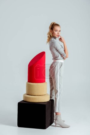 beautiful woman biting finger and posing near big red lipstick model on grey background