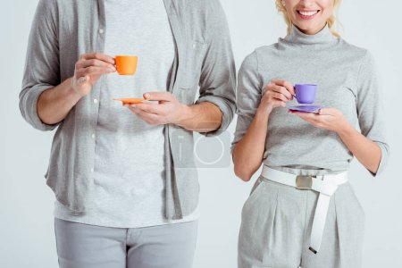 cropped view of couple holding colorful coffee cups isolated on grey