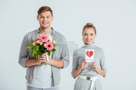 happy couple looking at camera and holding Valentines card with flower bouquet isolated on grey