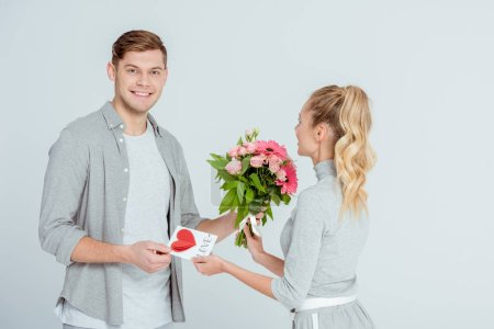 smiling man greeting woman with Valentines card and flower bouquet isolated on grey