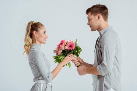 schöner Mann schenkt Frau einen rosafarbenen Blumenstrauß