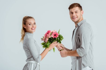 Handsome man giving flower bouquet to beautiful sm...