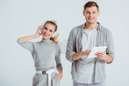 happy woman in headphones listening music while smiling man using digital tablet isolated on grey
