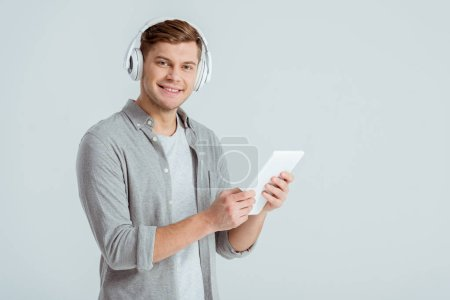 Photo for Man in headphones listening music, looking at camera and using digital tablet isolated on grey - Royalty Free Image