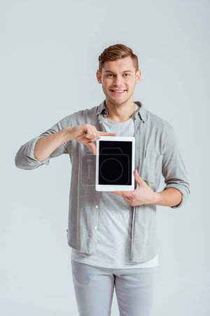 smiling man in grey clothing presenting digital tablet with blank screen isolated on grey