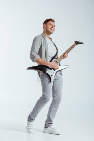 Photo for Excited smiling man in grey clothing playing electric guitar on grey background - Royalty Free Image