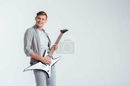 Photo for Excited handsome man in grey clothing playing electric guitar isolated on grey - Royalty Free Image