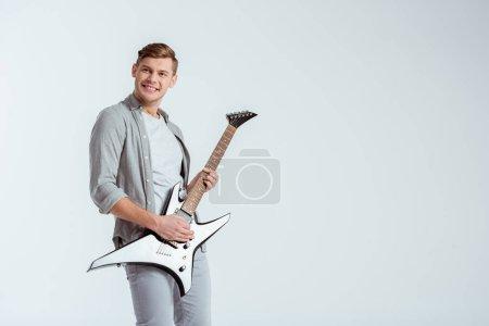 Photo pour Excité bel homme en vêtements gris, jouer de la guitare électrique isolé sur fond gris - image libre de droit