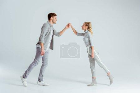 Photo pour Beau couple main dans la main et en regardant l'autre tandis que danse isolé sur fond gris - image libre de droit