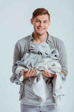 smiling handsome man looking at camera and holding pile of grey clothes isolated on grey