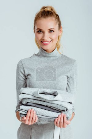 beautiful smiling woman looking at camera and holding pile of grey clothes isolated on grey