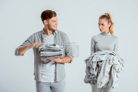 dissatisfied woman looking at smiling man holding grey clothes isolated on grey
