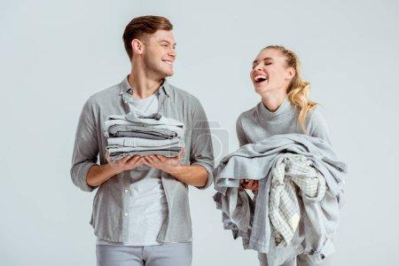 Photo pour Beau couple tenant des piles de vêtements gris et rire isolé sur fond gris - image libre de droit