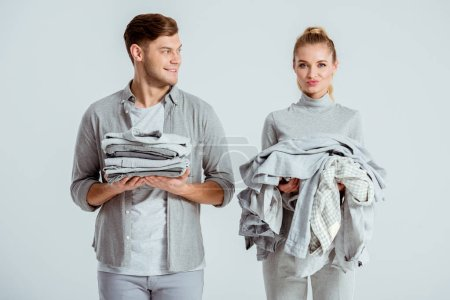 beautiful young couple holding piles of grey clothes isolated on grey