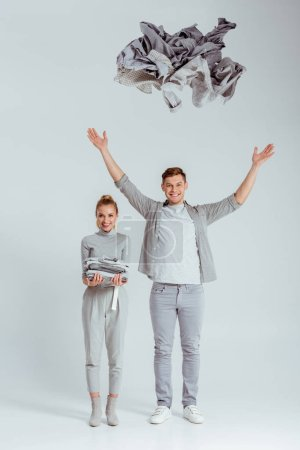 woman in grey outfit looking at camera and standing near man throwing pile of clothes in air on grey background