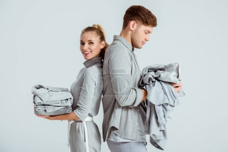 young couple in grey outfits holding grey clothes isolated on grey