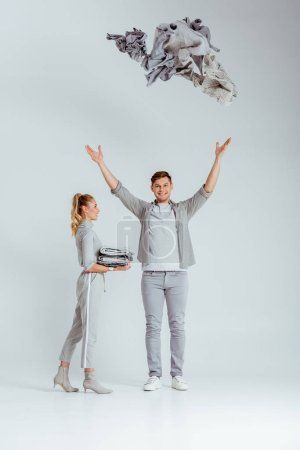 woman in grey outfit standing near man throwing pile of clothes in air on grey background