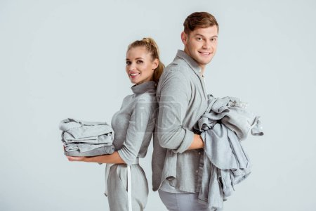 smiling couple looking at camera and holding grey clothes isolated on grey