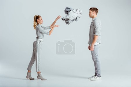 Photo for Smiling woman throwing pile of clothes at man on grey background - Royalty Free Image