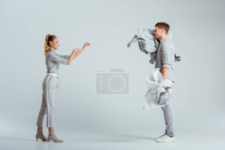 attractive woman throwing pile of clothes at man on grey background