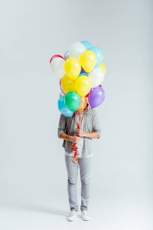 man in grey clothes hiding behind bundle of colorful balloons on grey background