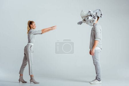 blonde woman throwing pile of clothes at man on grey background