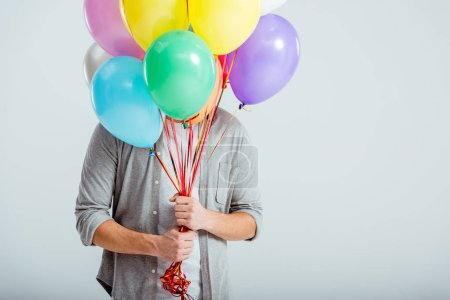 man in grey clothes hiding behind bundle of colorful balloons with copy space on grey background
