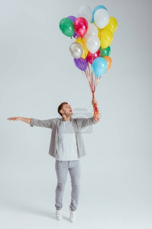 man in grey clothing standing on tiptoe and holding bundle of colorful balloons on grey background