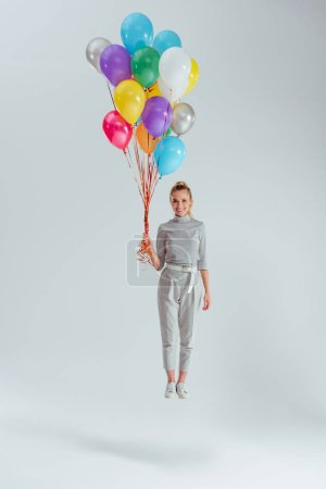 smiling woman looking at camera and jumping in air with bundle of colorful balloons on grey background