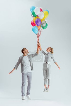 happy couple jumping with bundle of colorful balloons on grey background