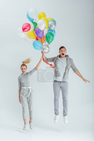 excited couple looking at camera and jumping with bundle of colorful balloons on grey background