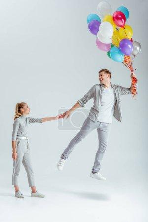 femme en vêtements gris, tenant la main de l'homme heureux sautant en l'air avec le paquet de ballons colorés sur fond gris
