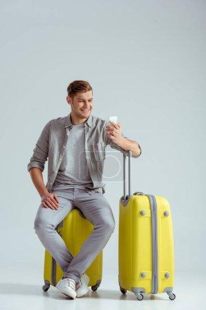 Photo pour Homme souriant assis sur une valise jaune et utilisant un smartphone sur fond gris, concept de voyage - image libre de droit