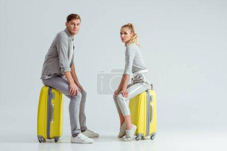 Photo pour Beau couple assis sur des valises et regardant la caméra sur fond gris, concept de voyage - image libre de droit