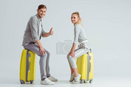 Photo pour Couple assis sur des valises tandis que l'homme montrant pouce vers le haut signe sur fond gris, concept de voyage - image libre de droit