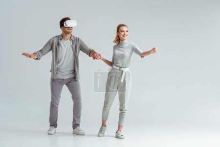 Photo for Happy couple holding hands while man experiencing virtual reality on grey background - Royalty Free Image