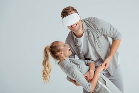 Photo for Man holding smiling woman in embrace while having virtual reality experience isolated on grey - Royalty Free Image