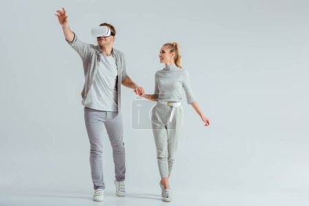 Photo for Couple holding hands while man experiencing virtual reality and gesturing on grey background - Royalty Free Image