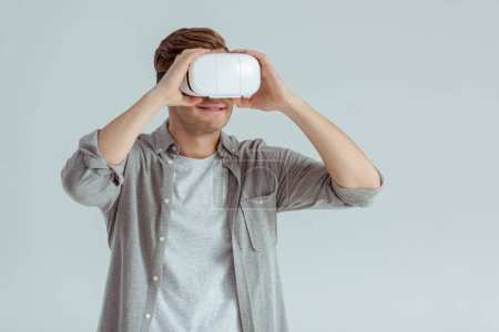 smiling man wearing virtual reality headset isolated on grey